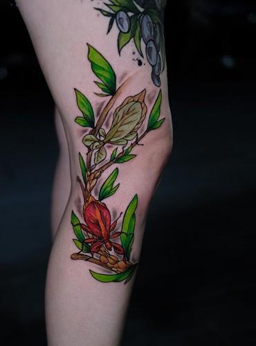 Florales Tattoo gestochen von dem Bein im farbenfrohen Tattoodesign